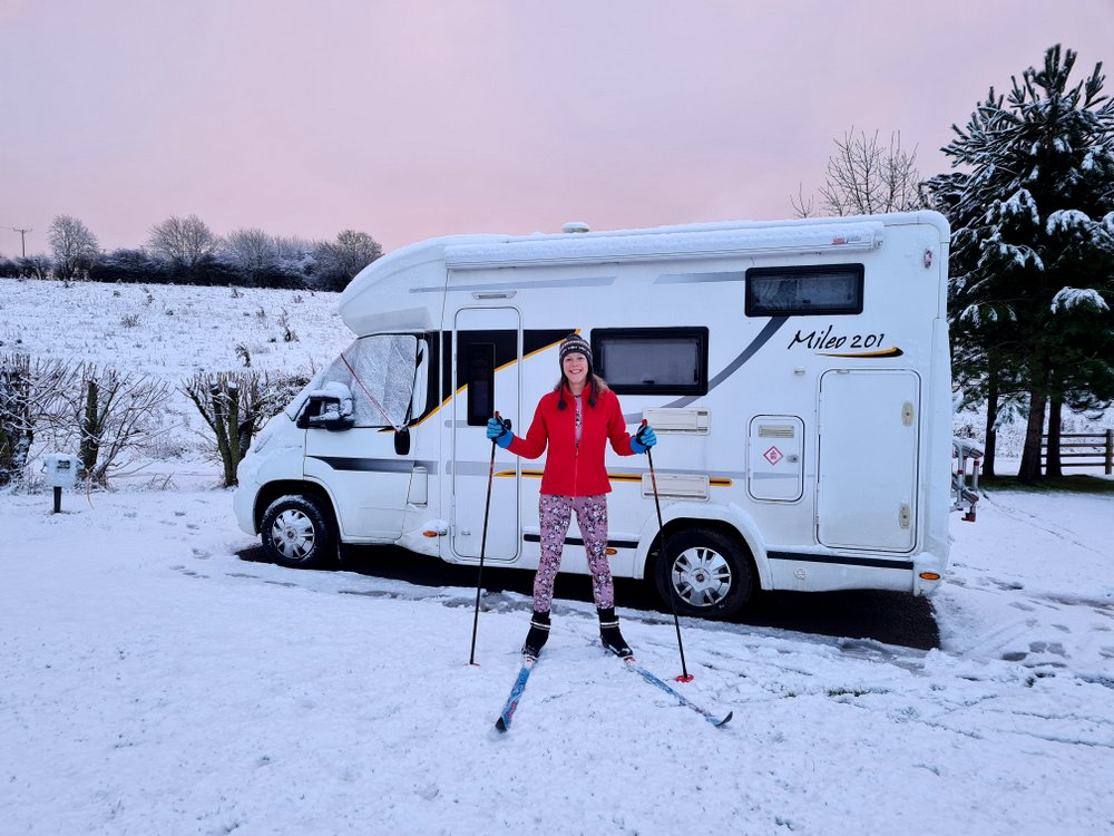 Van lifer and cross country skier Bev outside her winterised Benimar Mileo 201 motorhome enjoying the snow
